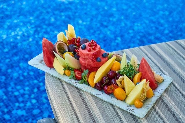 A plate of fruit by the water
