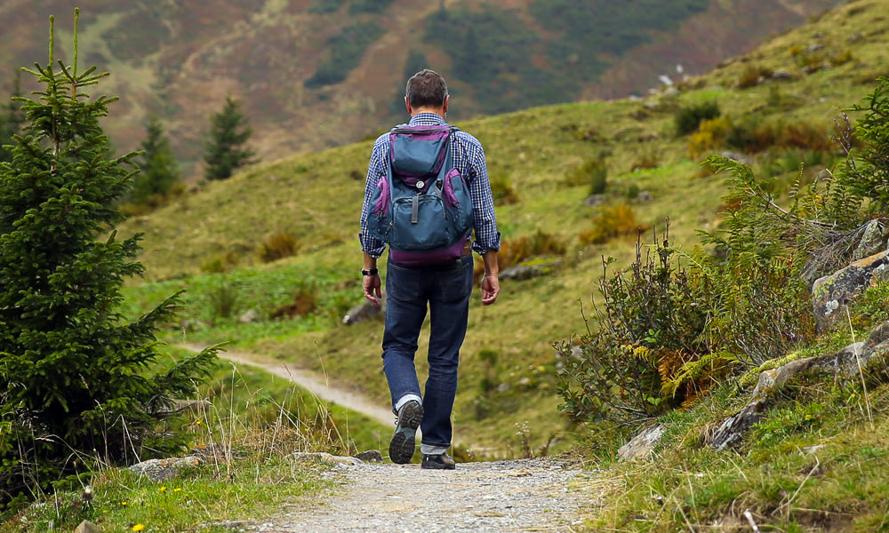 A man hikes in nature with hills and mountains in the distance