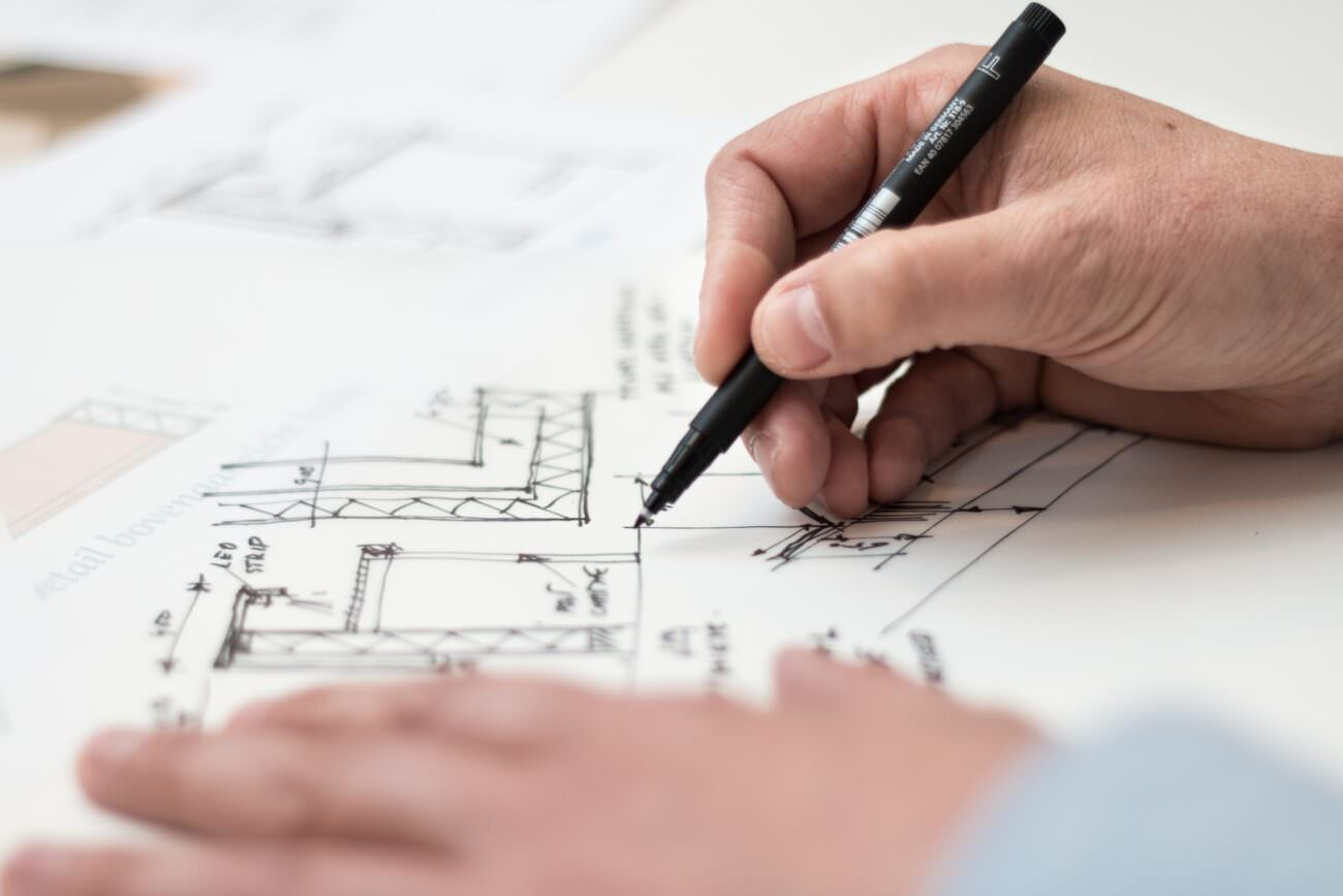 A businessperson is drawing a technical architectural sketch with a black pen