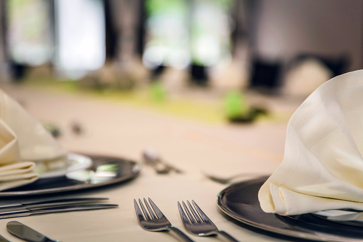 Plates, napkins, and cutlery are arranged on a table, ready for dinner