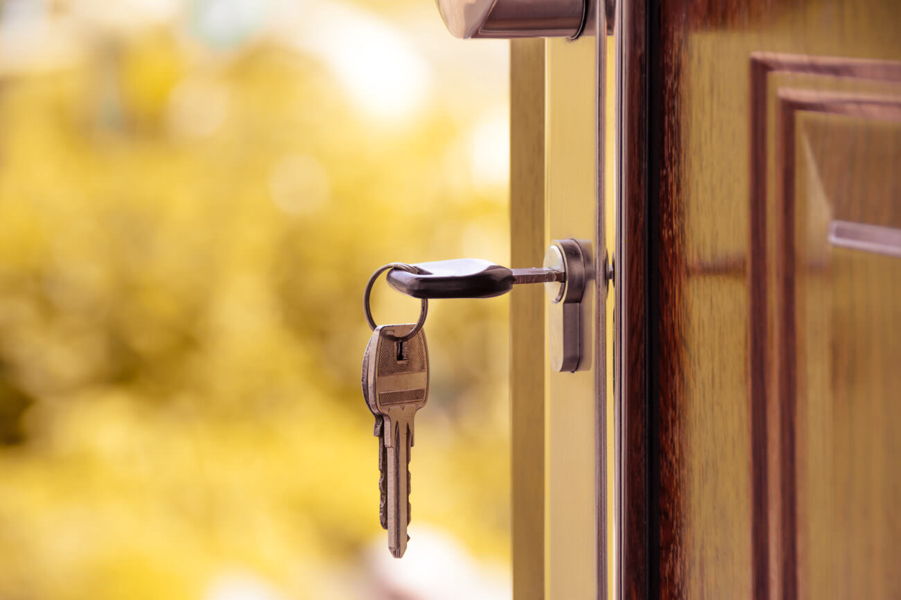 A key hangs from a lock on a door. The door is open, looking outwards, and it is bright and sunny outside with trees in the background. Someone is moving out of their house in November